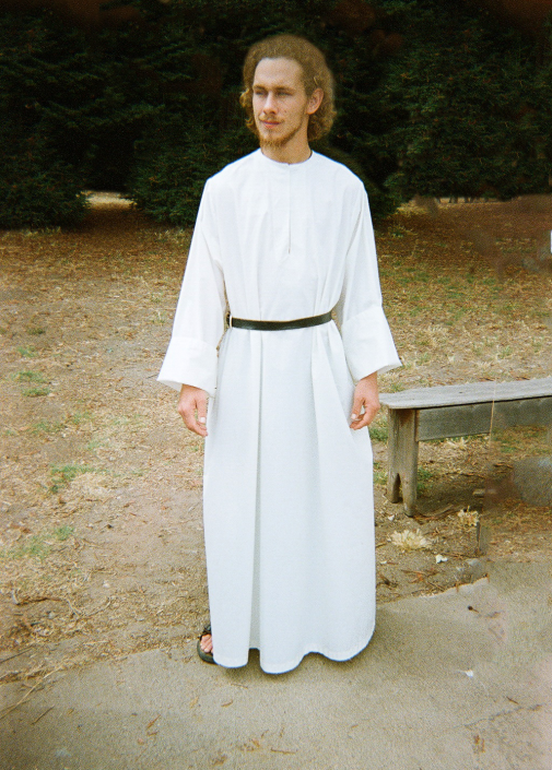 Young Benedictine monk in full length white tunic